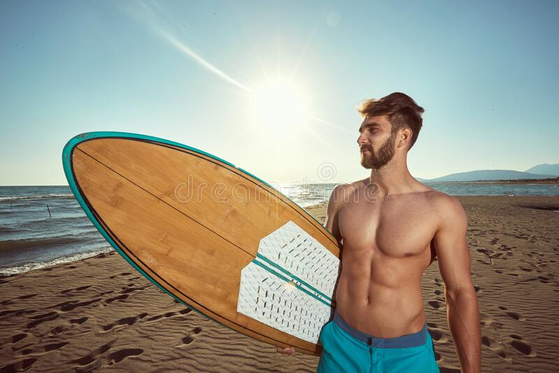 Fit young beardy male walking on the sunny beach, holding surfboard, smiling. uv protection concept royalty free stock image