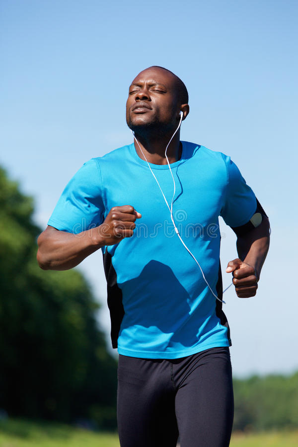Fit young black man running outdoors stock photography