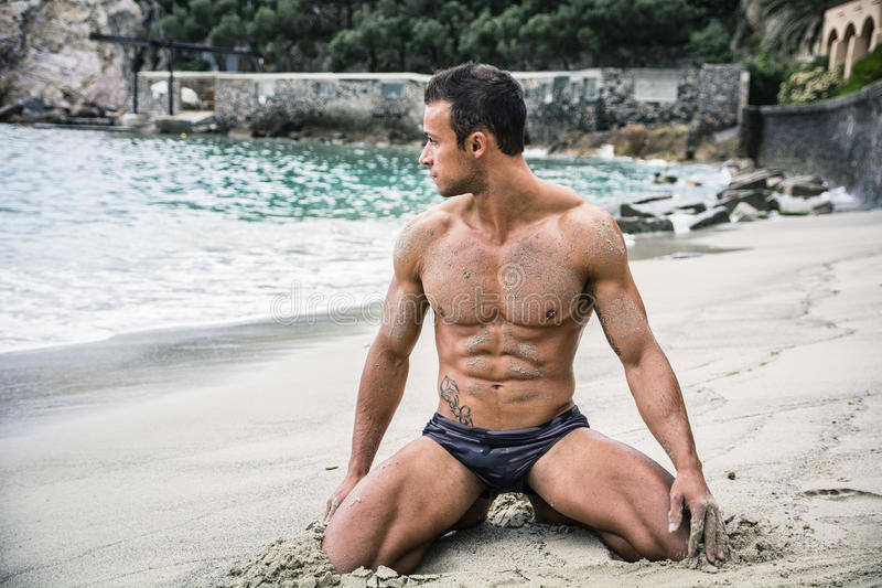 Fit young bodybuilder in bathing suit on the beach stock photo