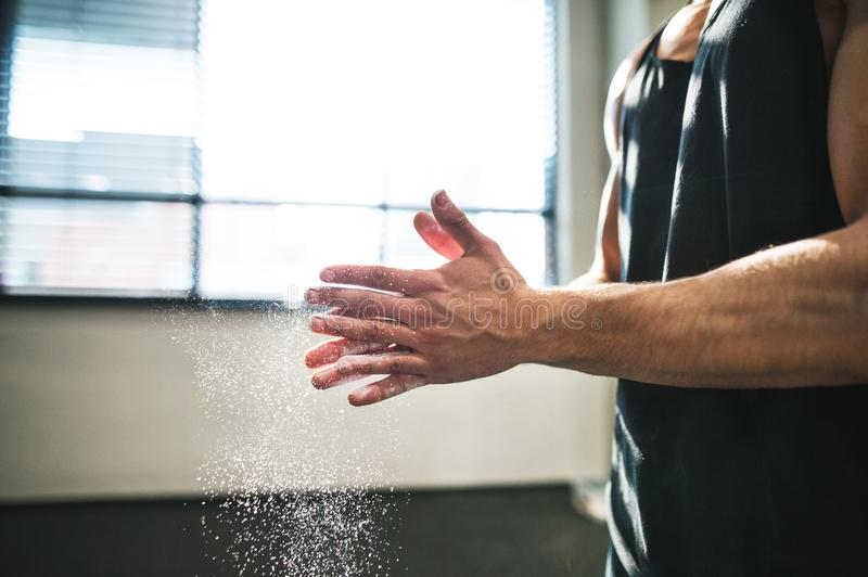Fit young man in gym smears his hands with magnesium. Close up. royalty free stock images