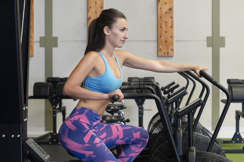 Fit young Caucasian woman using an air exercise bicycle at the gym or fitness studio royalty free stock photography