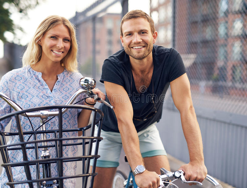 Fit young couple out enjoying a day cycling royalty free stock image