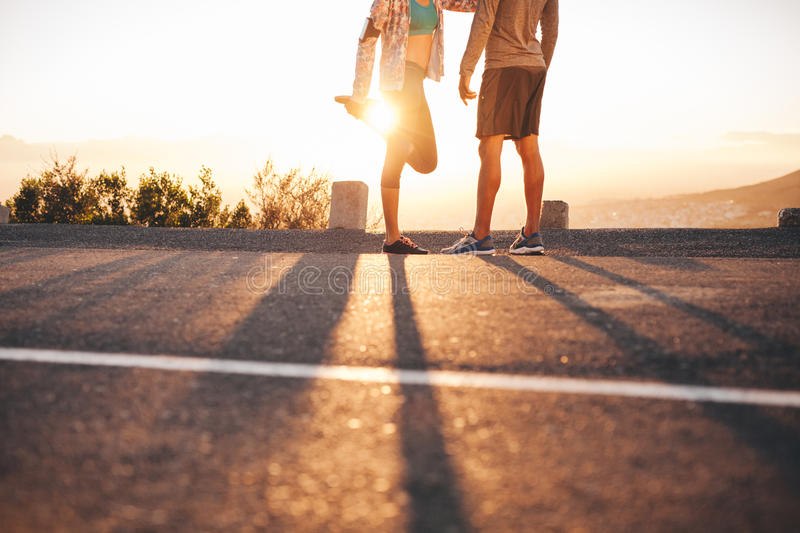 Fit young couple warming up before a run royalty free stock image