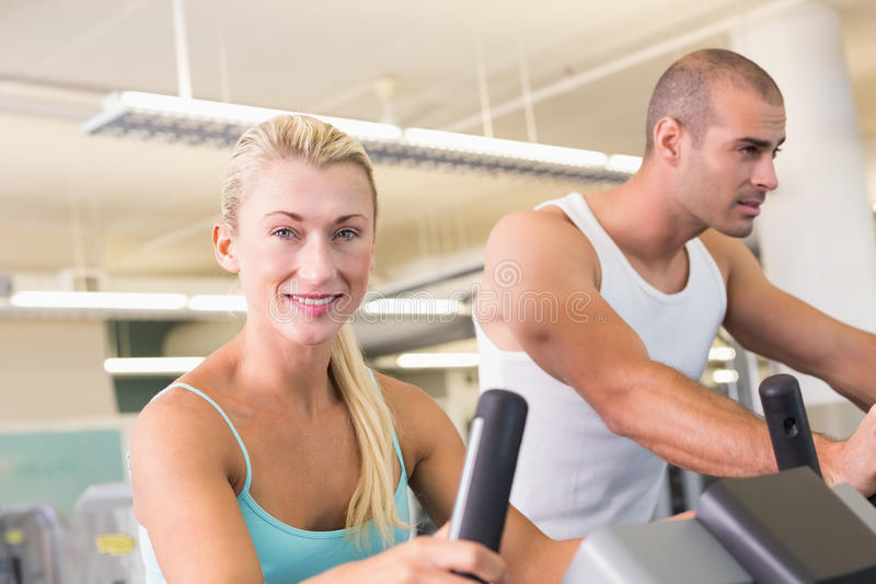 Fit young couple working on exercise bikes at gym. Portrait of a fit young couple working on exercise bikes at the gym stock photography