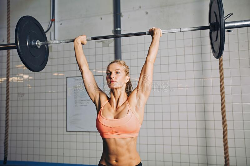 Fit young female athlete lifting heavy weights. Beautiful strong young woman with barbell and weight plates overhead. Fit young female athlete lifting heavy royalty free stock image