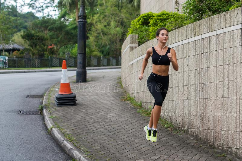 Fit young female jogger jogging on sidewalk in suburban area. Pretty girl working out outdoors. Fit young female jogger jogging on sidewalk in suburban area stock photography