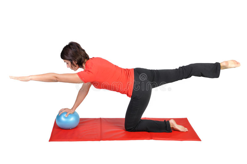 Fit young female pilates instructor. Showing different exercises with ball on a white background royalty free stock photos