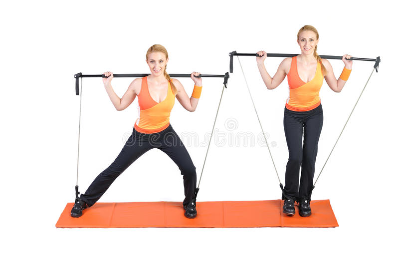 Fit young female pilates instructor. Showing different exercises on a white background royalty free stock images