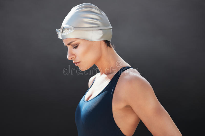 Fit young female swimmer. Side view of fit young female swimmer on black background. Fitness woman in swimming costume concentrating stock photography