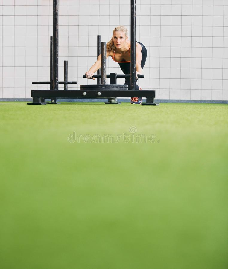 Fit young female using prowler exercise equipment at gym. Strong young woman pushing the prowler on artificial grass turf. Fit female using prowler exercise royalty free stock photos