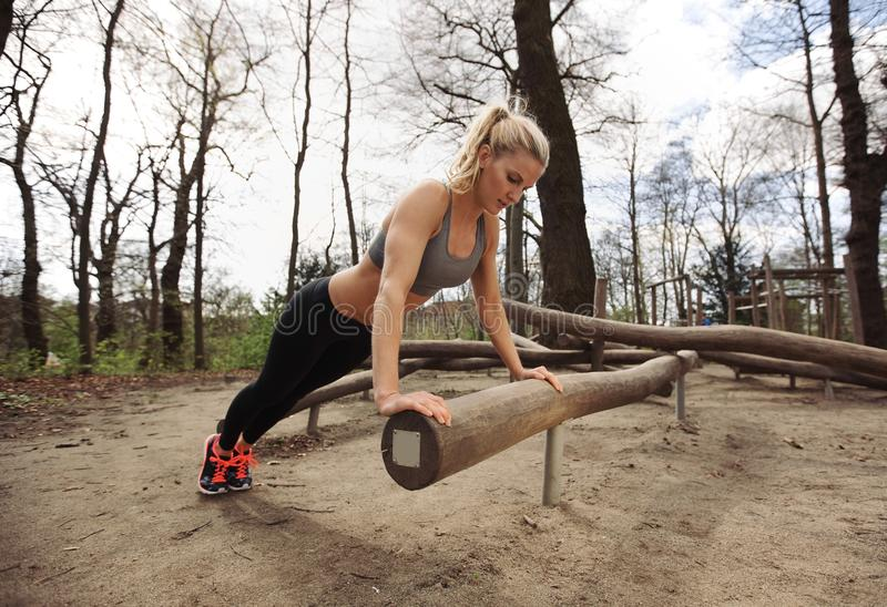 Fit young lady exercising in park. Strong and muscular young female doing pushups on a log royalty free stock photos