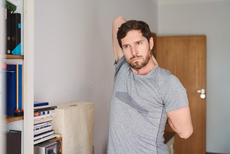 Young man in sportswear stretching before working out at home. Fit young man in exercise clothing stretching his arms and warming up before working out in his royalty free stock image