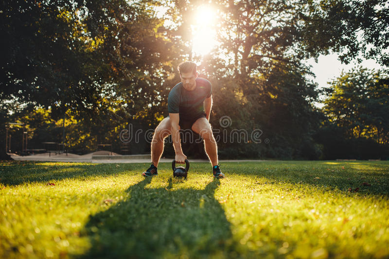 Fit young man exercising with kettlebell outdoors royalty free stock photo