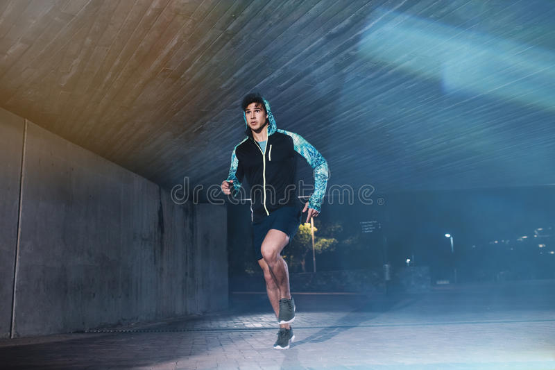 Fit young man jogging in the city at night stock photo