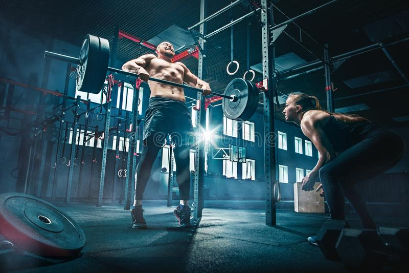 Fit young man lifting barbells working out in a gym. Fit young men lifting barbells working out at a gym. Sport, fitness, weightlifting, bodybuilding, training royalty free stock photos