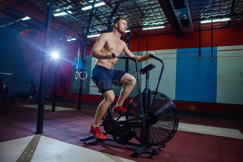 Fit young man using exercise bike at the gym. Fitness male using air bike for cardio workout at cross training gym. stock photos