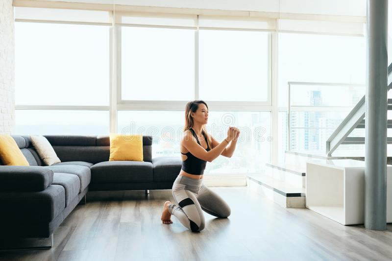 Adult Woman Training Legs Doing In and Out Squat. Fit young Pacific Islander woman training at home. Beautiful female athlete working out for wellbeing in stock photography