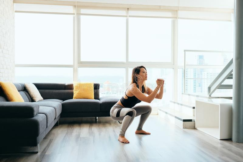 Adult Woman Training Legs Doing In and Out Squat. Fit young Pacific Islander woman training at home. Beautiful female athlete working out for wellbeing in royalty free stock photos