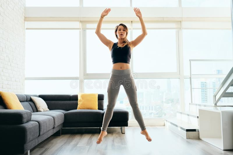 Adult Woman Training Legs Doing Squat and Jumping. Fit young Pacific Islander woman training at home. Beautiful female athlete working out for wellbeing in royalty free stock images
