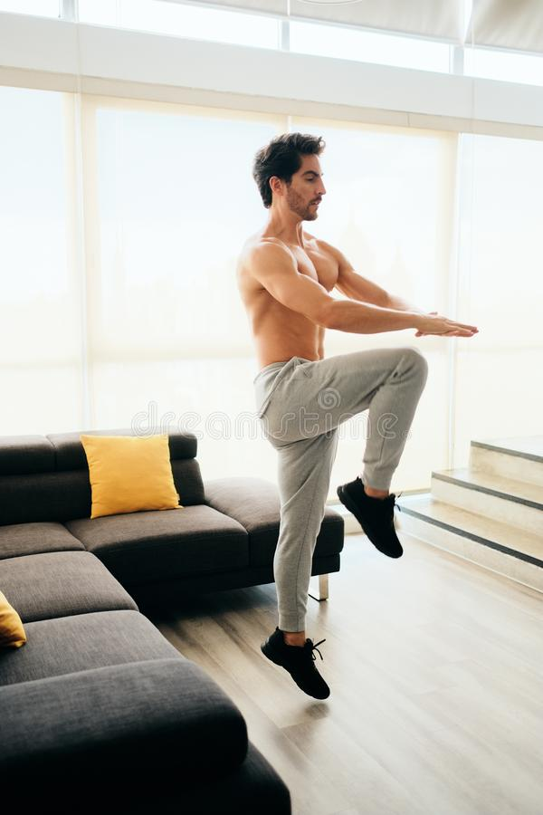 Adult Man Training ABS and Legs Doing High Knee Tap. Fit young white man training at home. Handsome hispanic male athlete working out for wellbeing in domestic royalty free stock image