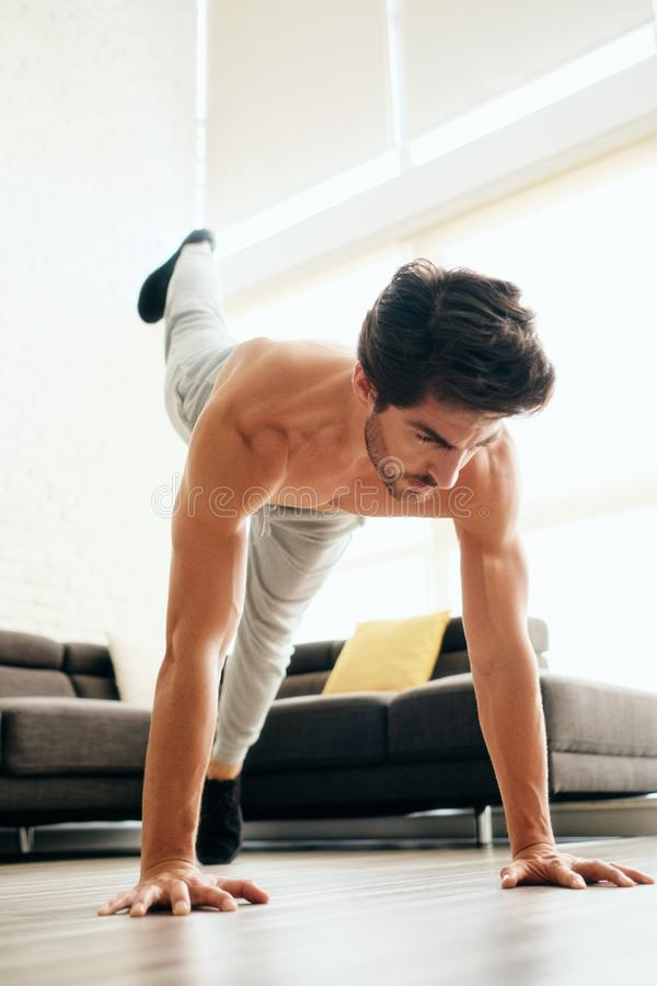Man Training Legs and Back Muscles Doing Plank with Leg Lift. Fit young white man training at home. Handsome hispanic male athlete working out for wellbeing in royalty free stock photo