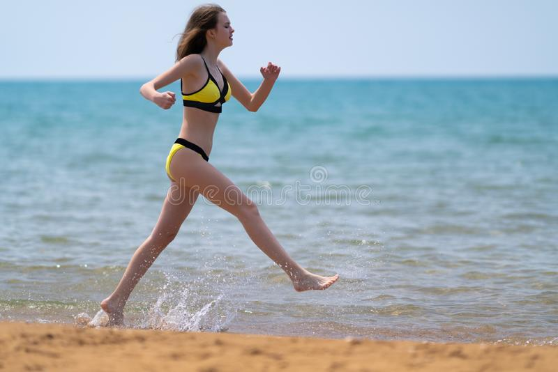 Fit young woman in a bikini running in the sea royalty free stock photo