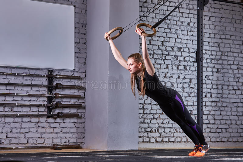Fit young woman in the black sportwear exercising with gymnastic rings in gym against brick wall. royalty free stock photography