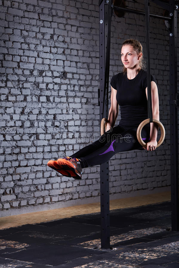 Fit young woman in the black sportwear exercising with gymnastic rings in gym against brick wall. stock images