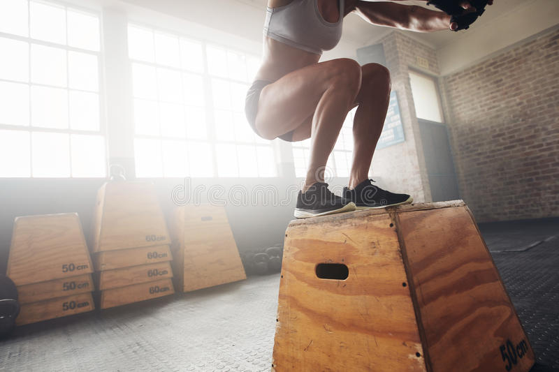 Fit young woman box jumping at a crossfit gym. Female athlete is performing box jumps at gym, with focus on legs royalty free stock photography