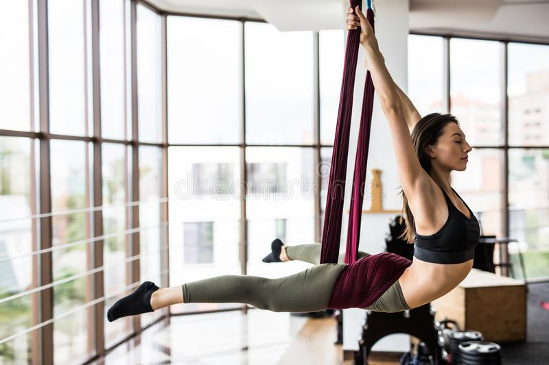 Fit pretty young woman doing fly yoga stretching exercises in fitness training at gym hall . Sport and healthy lifestyle concept. royalty free stock photo