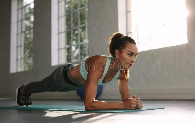 Fit young woman doing push ups at gym. Healthy young female working out on exercise mat stock photo