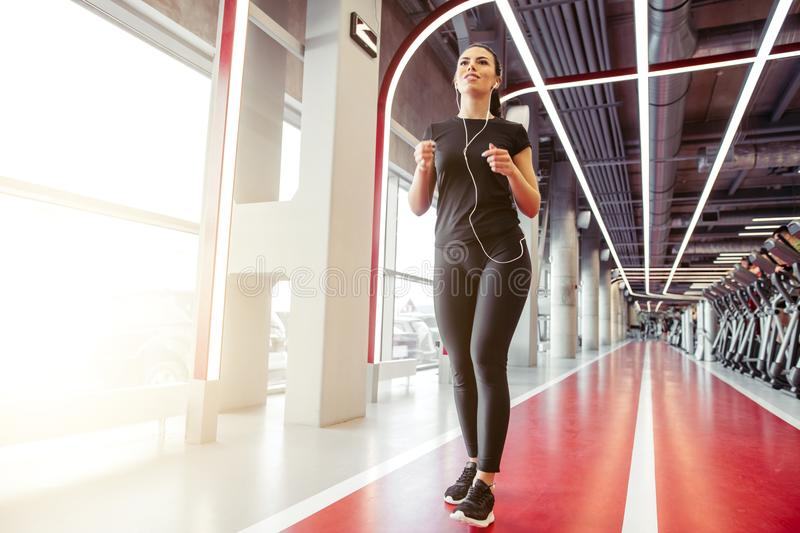 Woman with earphones running on indoor track at gym. Fit young woman with earphones jogging on indoor track at gym royalty free stock images