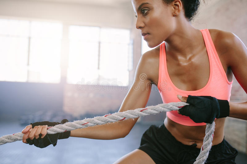 Fit young woman exercising with rope at a gym stock photos