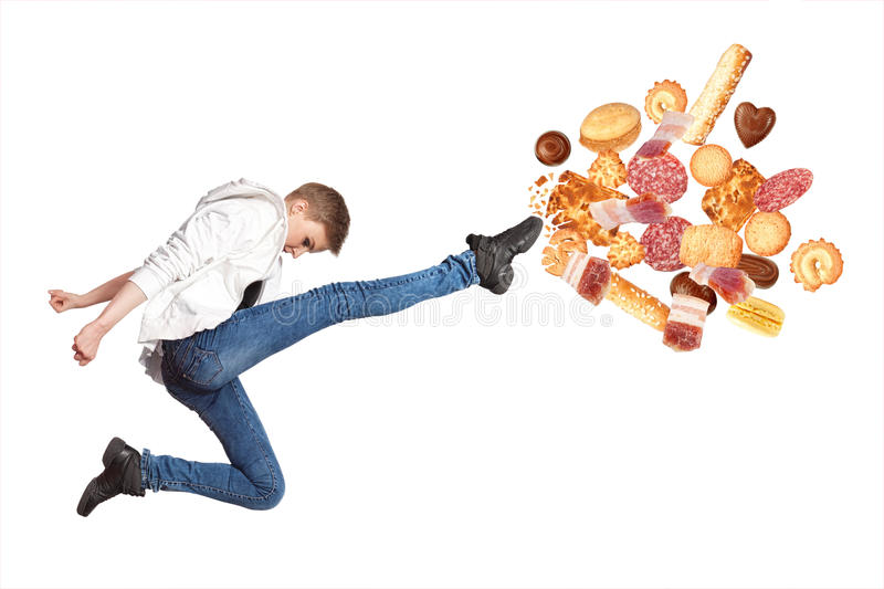 Fit young woman fighting off bad food stock images