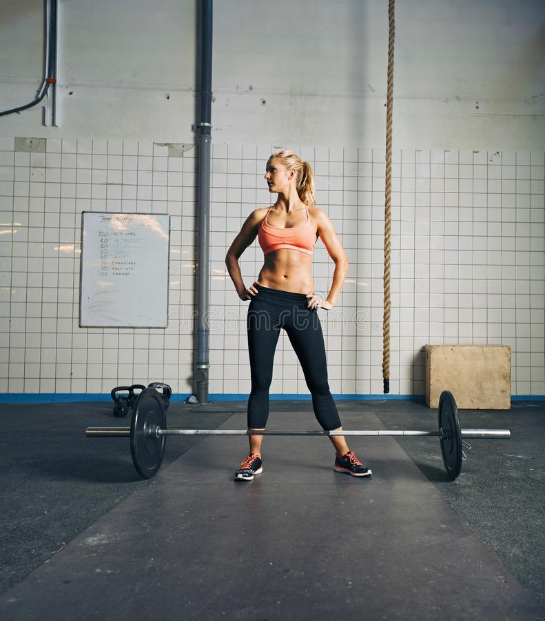 Fit young woman at gym with barbell. Fit young woman standing at gym with barbell on floor. Strong and muscular crossfit female at gym royalty free stock photo