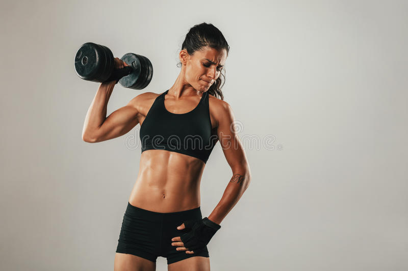 Fit young woman holding a dumbbell aloft. Fit strong muscular young woman holding a dumbbell aloft with a grimace and look of fierce concentration and effort stock photography