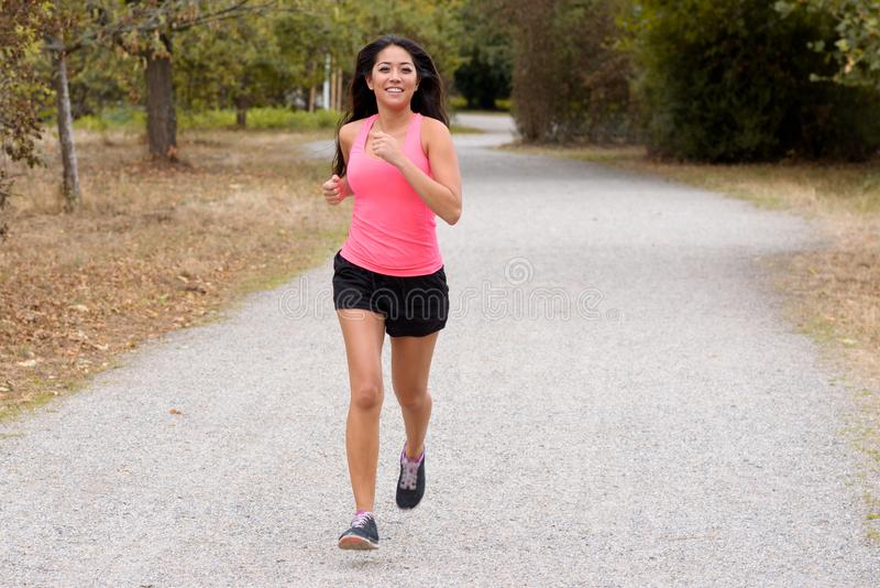 Fit young woman jogging on a country road royalty free stock photo