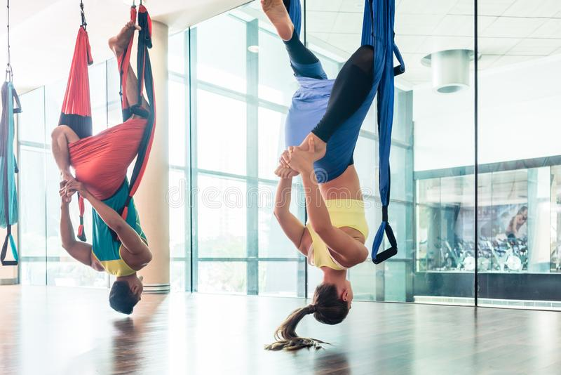 Fit young woman practicing aerial yoga in a modern fitness club royalty free stock image