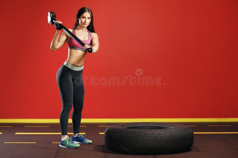 Fit young woman preparing for workout in the gym with hammer and tractor wheel. stock images