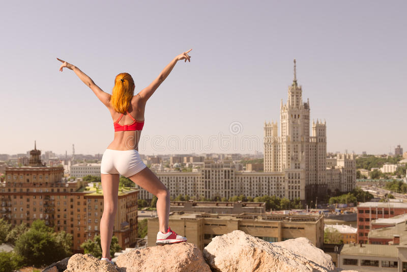 Fit young woman with raised hands above the city. On top of mountain royalty free stock photos