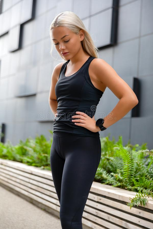 Fit young woman rests with hands on her hips and smiling. royalty free stock photography
