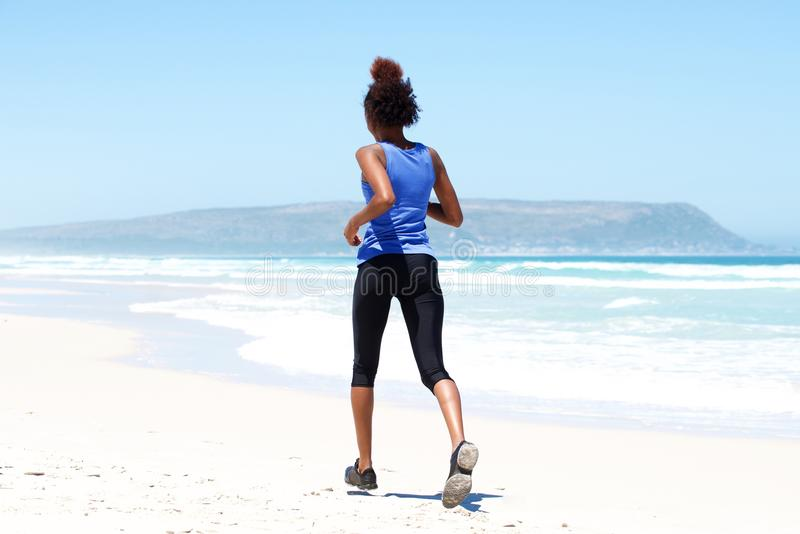 Fit young woman running on the beach royalty free stock image