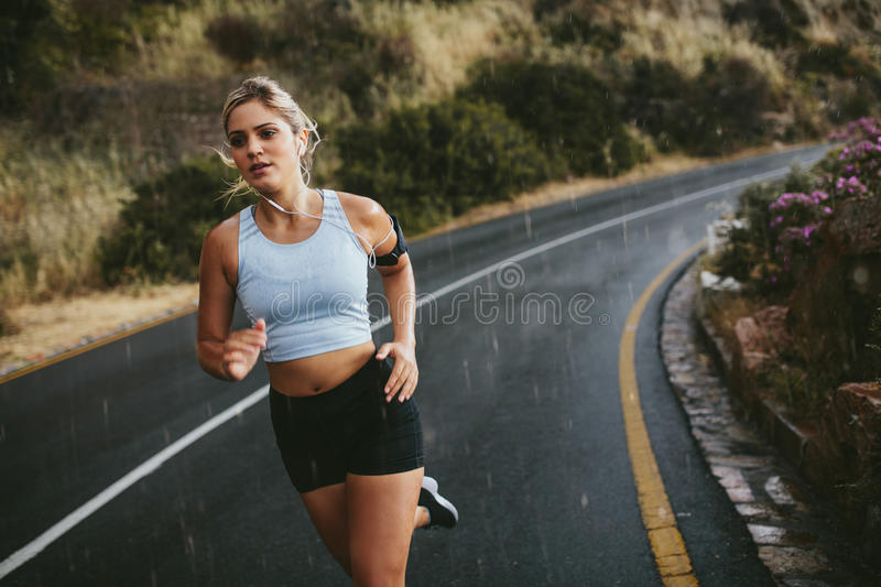 Fit young woman running on highway stock photos