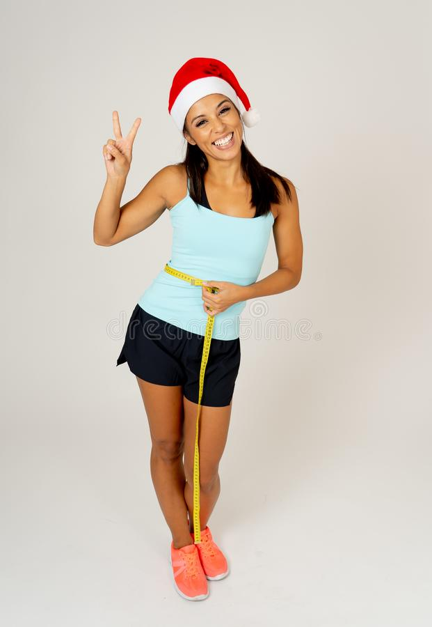 Fit young woman in Santa hat measuring her waist feeling happy and showing victory and ok gestures stock image