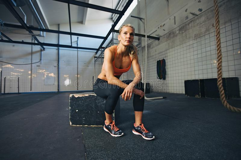 Fit young woman sitting at crossfit gym. Young woman sitting on a box at crossfit gym looking away. Fit young caucasian female athlete at gym royalty free stock photo