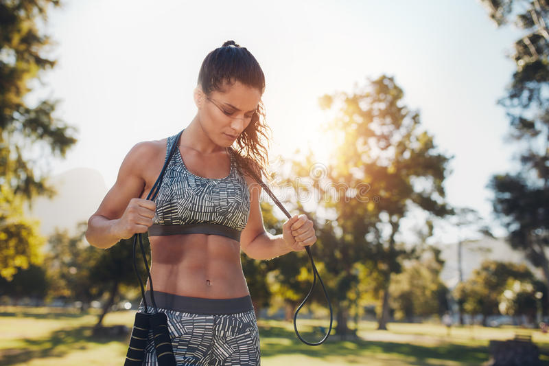 Fit young woman with a skipping rope at the park. Fit young woman holding a skipping rope around her neck. Female athlete taking a break from fitness training at stock photo