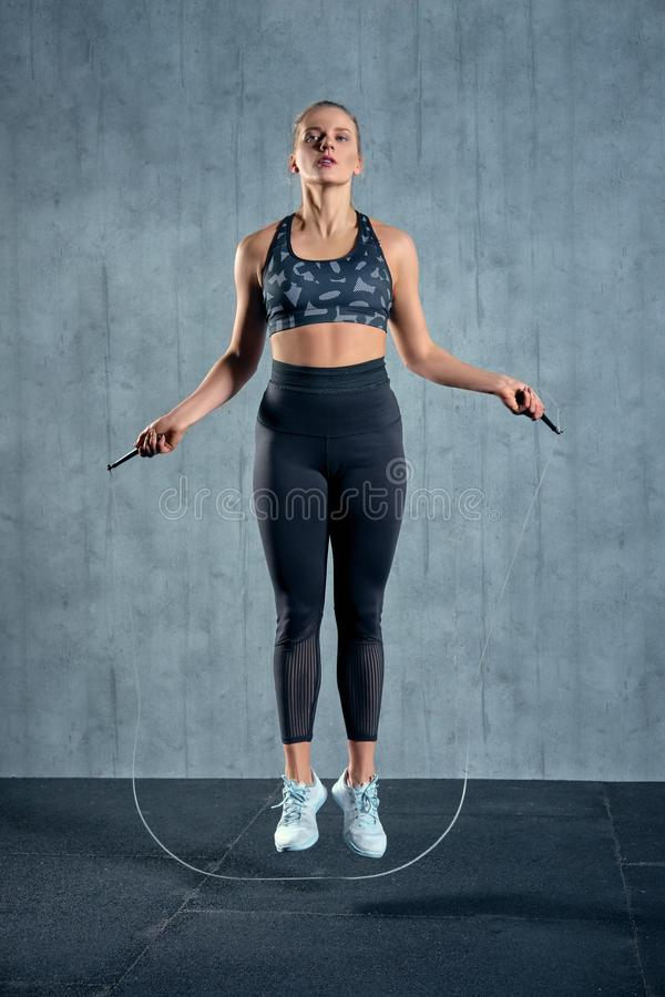 Portrait of muscular young woman exercising with jumping rope on grey background. royalty free stock photography