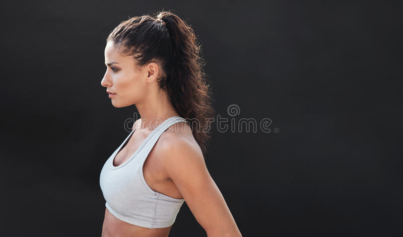 Fit young woman in sports bra. Side view of fit young woman in sports bra looking away on black background stock photos