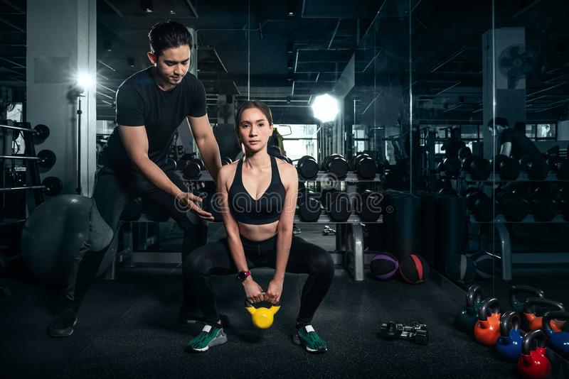 Fit young woman in sportswear focused on lifting a dumbbell during an exercise class in a gym royalty free stock photo