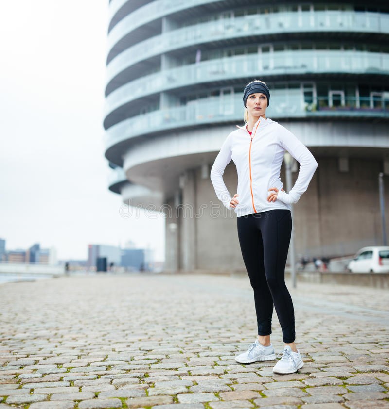 Fit young woman in sportswear standing on street. Full length image of fit young woman in sportswear standing on street looking away. Confident female athlete on stock photos